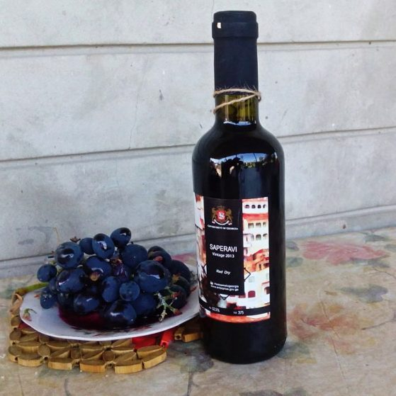 Vachtang guesthouse: bottle of red wine and plate of grapes on the table