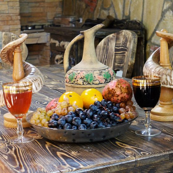 Mountain Scream family hotel: the plate full of fruits and glasses filled with white and red wine on the wooden table