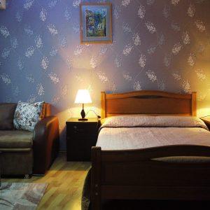Mountain Scream šeimos viešbutis: kambarys su dvigule lova bei patogia sofa šalia medinio stalo
