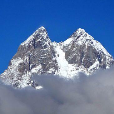 Gražiausios Gruzijos vietos: Ušbos viršūnė, išnirusi iš debesų mėlyno dangaus fone