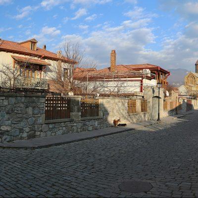 Gruzijos gamtoje: Mcheta miesto gatvės fragmentas su bažnyčia tolumoje