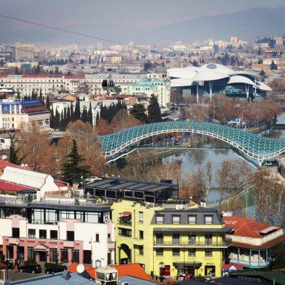 Gruzijos gamtoje: panoraminis Tbilisio miesto vaizdas su įspūdingu tiltu per upę ir tolumoje esančiais Teisingumo rūmais