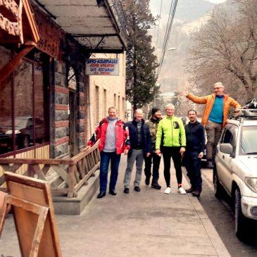 Slidinėjimo kurortai Gruzijoje: džiaugsmingų vyrų kompanija, stovinti gatvėje priešais restoraną
